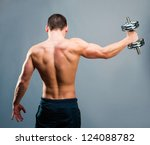 Rear view of a young male bodybuilder doing heavy weight exercise with dumbbells against gray backg - stock photo