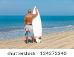 young man holding surfboard on beach in Bali - stock photo