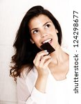 Portrait of a beautiful, latin Woman eating chocolate. - stock photo