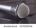 A Microphone over a black reflecting surface - stock photo