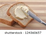 A knife spreading butter on wheat bread - stock photo