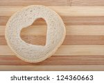Heart shaped hole in a slice of bread - stock photo