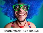 Funny guy naked with blue wig and red tie on blue background - stock photo