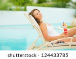 Young woman in swimsuit relaxing with cocktail on chaise-longue - stock photo