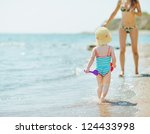 Baby running to mother along seashore - stock photo