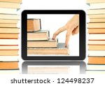 Black tablet like ipade and books around. Fingers go up on the books in tablet. Concept of growth up when you reading books - stock photo