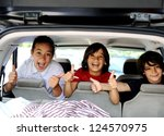 Smiling happy children in car with thumb up - stock photo