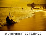 sand beach, people swimming and ride on kite on sunset. - stock photo