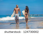 Young couple walking on beach with surfboards in arm - stock photo