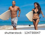 Young couple running on beach with surfboards in arm - stock photo