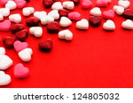 Colorful Valentines Day heart shaped candy border on red paper background - stock photo