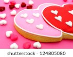 Heart shaped Valentines Day cookies and candies on pink paper background - stock photo