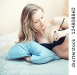 Woman in black camisole laying in bedroom - stock photo