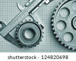 gears and caliper on graph paper - stock photo