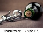 wine bottle and metal corkscrew - stock photo