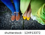 Couples legs dressed in bright colorful shoes - stock photo