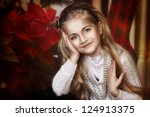 Beautiful little girl holding her hands near the face on christmas style background - stock photo