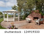 Nice backyard patio with gazebo and big brick fireplace - stock photo