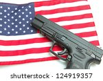 American Firearm/Autoloader handgun laying on US flag - stock photo