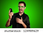 scared man holding phone on green background - stock photo