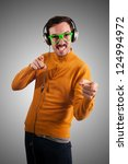 guy with headphones listening to music on green background - stock photo