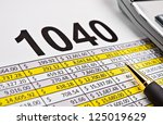 Spread sheet, tax form 1040 with pen and calculator. - stock photo