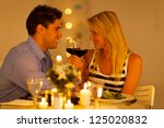 loving young couple enjoying a glass of wine in restaurant - stock photo