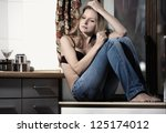 Sad woman sitting at the kitchen - stock photo