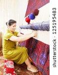 smiling carpet weaver at work... | Shutterstock . vector #125195483