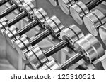 A rack of silver colored dumbbells. - stock photo
