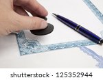 Businessman (or notary public) in office stamping document - stock photo