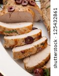 Closeup of delicious sliced roast pork tenderloin with olives, vermouth, and citrus. - stock photo