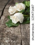 Stock photo three white roses on the wooden table 125471687
