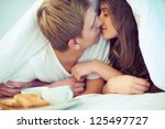 Young amorous couple kissing under blanket - stock photo