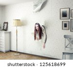 woman climbs through the wall into the room - stock photo