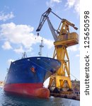 Large harbor cranes and a big container ship - stock photo