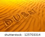 Text in desert sand Dubai - stock photo
