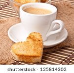 heart-shaped toast  and a cup of coffee - stock photo
