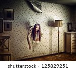 angry woman climbs through the wall into the room (photo and hand-drawing elements compilation. texture and grain add) - stock photo