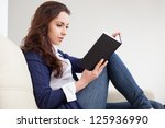 young woman reading a book on the couch - stock photo