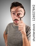 man looking through a magnifying lens on gray background - stock photo