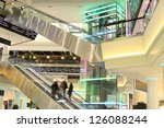 mall with escalators and people in motion - stock photo