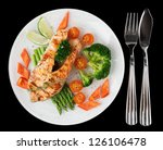 Grilled salmon steaks in white plate, isolated on black background - stock photo