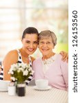pretty young woman and grandmother having coffee together - stock photo