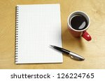 Cup of coffee and notepad on a wooden table - stock photo