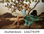 Beautiful Woman In Blue Fluttering Dress Swinging On A Beach Swing - stock photo
