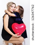 happy mother and her daughter with big red balloon - stock photo