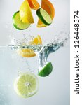 Lemon, lime and orange splash in clear water - stock photo