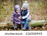 Two sisters sitting on a tree on early spring or late autumn - stock photo
