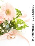 Gerbara bouquet and golden wedding ring with ribbon - stock photo